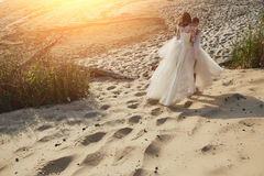 Photoshoot lovers in a wedding dress on the beach near the sea.  Royalty Free Stock Photo