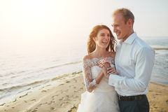 Photoshoot lovers in a wedding dress on the beach near the sea.  Royalty Free Stock Photos
