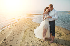 Photoshoot lovers in a wedding dress on the beach near the sea.  Stock Photo