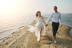 Photoshoot lovers in a wedding dress on the beach near the sea.  Stock Image