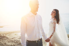 Photoshoot lovers in a wedding dress on the beach near the sea.  Royalty Free Stock Photography