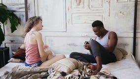 Photoshoot på pijamas i morgon Blandras- par på sängen Man att ta foto av kvinnan på gammal flyttning-film kamera lager videofilmer
