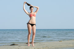 Photoshooting of a beauty pageant winner. Winner of beauty pageant in Greece ,wearing bikini walking tip toe on sand, making ponytail her hair, Aegean sea as Stock Photography