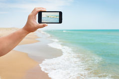 Photoshooting on smartphone at sea. Coast Stock Photos