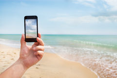 Photoshooting on smartphone at sea. Coast Royalty Free Stock Images