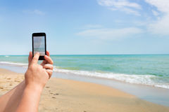 Photoshooting on smartphone at sea Stock Photography