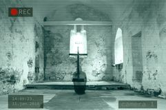 A Photoshop of a CCTV image of a hooded ghost kneeling next to a cross in a disused church. stock photography