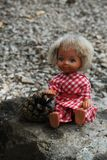 Phototeries - Blue eyes doll with a pinecone Royalty Free Stock Photography
