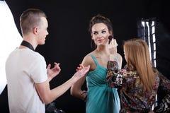 Phototograper, artista de maquillaje y modelo trabajando junto Foto de archivo