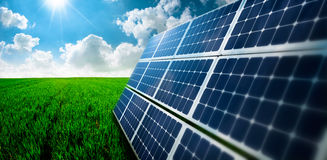 Photovoltaic ecological modules in grass. Photovoltaic ecological modules on grass valley against of sun behind cloudy sky Royalty Free Stock Image