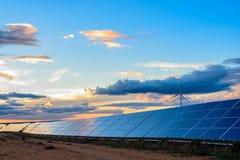 Photovoltaic en windinstallatie bij zonsondergang stock afbeeldingen