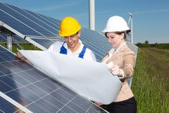 Photovoltaic engineers with construction plan at solar panels Royalty Free Stock Photo