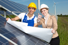 Photovoltaic engineers with construction plan at solar panels Stock Images