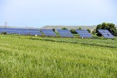Photovoltaic paneler i grönt fält arkivbilder