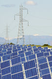 Photovoltaic panels. Huge solar field and high tension poles Stock Photos