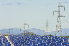 Photovoltaic panels. Huge solar field and high tension poles Royalty Free Stock Photo