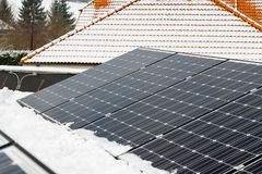 Photovoltaic panels on the roof cover with snow, in the winter Stock Image