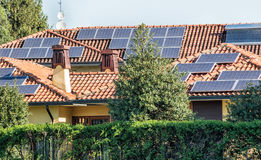 Photovoltaic solar panels on residential homes. Photovoltaic solar panels on the tiled roofs of residential homes providing alternate energy and electricity from Royalty Free Stock Photo