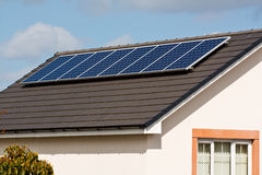 Photovoltaic Solar Panels on tiled roof. Photovoltaic Solar panels Mounted on a new tile roof of a modern home Royalty Free Stock Image