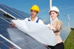 Photovoltaic teknikerer med konstruktionsplan på solpaneler Royaltyfri Bild