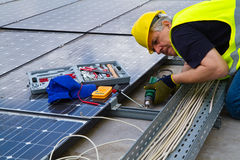 Photovoltaic worke. Fitting photovoltaic panels on a roof  of a building Stock Images