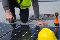 Photovoltaic worker. Photovoltaic worke fitting the panels on a roof Stock Photography