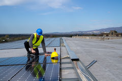 Photovoltaic worker. Photovoltaic worke fitting the panels on a roof Royalty Free Stock Photo