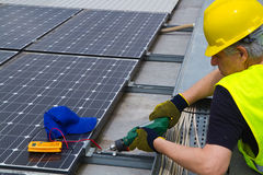 Photovoltaic worker. Photovoltaic worke in a roof working to fix it Royalty Free Stock Image