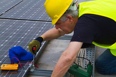 Photovoltaic worker. Photovoltaic worke in a roof working to fix it Stock Photography