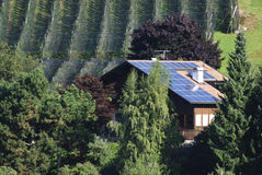 Photovoltaics. House with solar collectors at an apple plantation Stock Photos