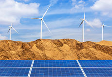 Photovoltaics solar cells and wind turbines generating electricity in desert. Royalty Free Stock Photo