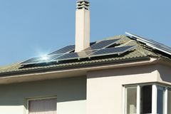 Photovotaic solar panels house roof. Sunny day beams reflections Stock Image