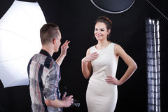 Photographer telling compliment to his model. During photoshooting royalty free stock image