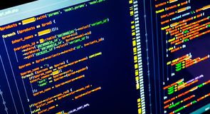 PHP code on the screen, extreme close up. Web developing and programming concept. PHP code on the screen, extreme close up. Orange, green and yellow coding stock photo