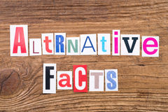 Phrase `Alternative Facts` on wooden background. Phrase `Alternative Facts` in cut out magazine letters on wooden background royalty free stock images