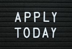 The phrase Apply Today in white text on a black letter board. The phrase Apply Today in white plastic letters on a black letter board as a reminder stock photo