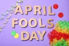 Phrase `April fools day` and rainbow wig. On color background Stock Images