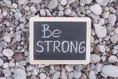 Phrase Be Strong on blackboard. Stone background. Close up Royalty Free Stock Photo