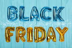 Phrase BLACK FRIDAY made of foil balloon letters on blue wooden background