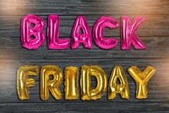 Phrase BLACK FRIDAY made of foil balloon letters on wooden background