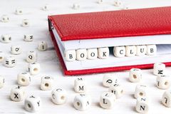 Phrase Book club written in wooden blocks in red notebook on white wooden table. Wooden abc royalty free stock photography