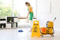 Safety sign, mop bucket with cleaning supplies and young woman on background. Phrase Caution wet floor on safety sign, mop bucket with cleaning supplies and royalty free stock photos