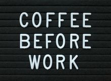 The phrase Coffee Before Work in white text on a letter board Royalty Free Stock Photography