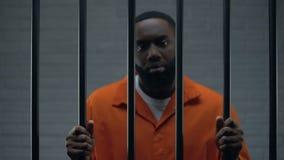 Phrase de attente noire de prisonnier masculin en cellule de prison, regardant tristement à la caméra clips vidéos