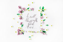 Phrase `Do small things with great love` written in calligraphy style on paper with wreath frame with lilac and chamomile Stock Photo