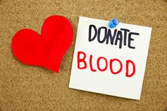 A yellow sticky note writing, caption, inscription Phrase DONATE BLOOD in black ext on a sticky note pinned to a cork. Phrase DONATE BLOOD in black ext on a royalty free stock photography