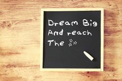 The phrase dream big written on chalkboard. And smiley face icon Royalty Free Stock Image