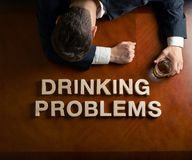 Phrase Drinking Problems and devastated man Stock Photos