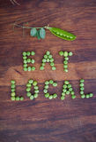 """Phrase """"Eat Local"""" made of green peas and pea pod with leaves Royalty Free Stock Images"""