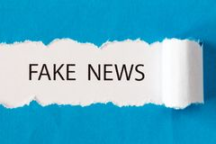 Phrase FAKE NEWS. Written under torn paper Royalty Free Stock Images